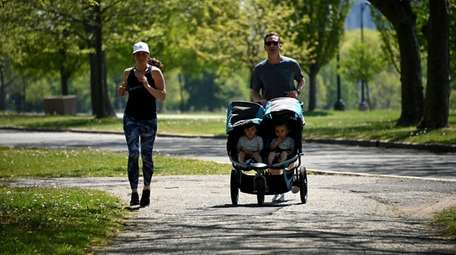 A family jogs together on a summerlike day