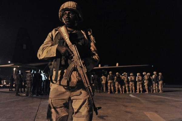 A soldier stands guard as Nigerian troops arrive