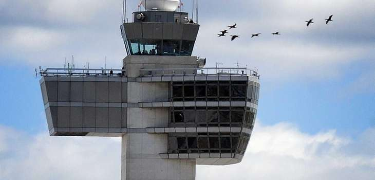 Birds fly past the control tower at New