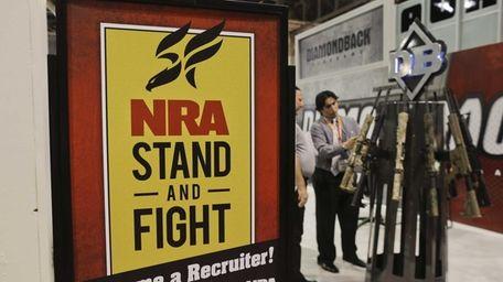 A Diamondback Firearms representative, rear right, explains features