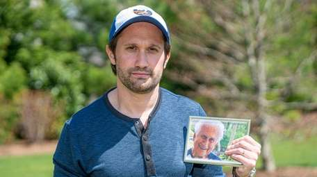 Tyler Gildin holds a photo of his late