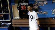 The Marlins' Dee Gordon touches the jersey honoring