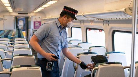 A Long Island Rail Road conductor takes a