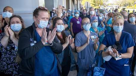 Healthcare workers applaud Anthony Greco.