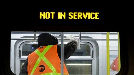 An MTA worker works helps disinfect a train
