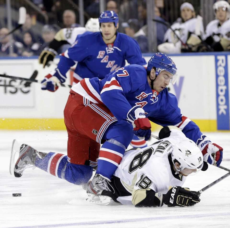 Rangers' Ryan McDonagh (27), top, becomes entangled with
