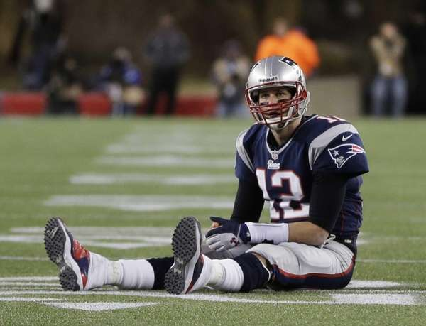 New England Patriots quarterback Tom Brady sits on