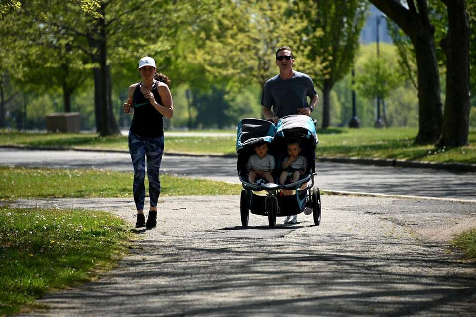 A family jogs together on a summer-like day