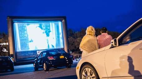 Attendees watch from their cars at a drive-in