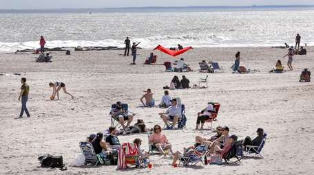 Groups of beachgoers gather on the shore at