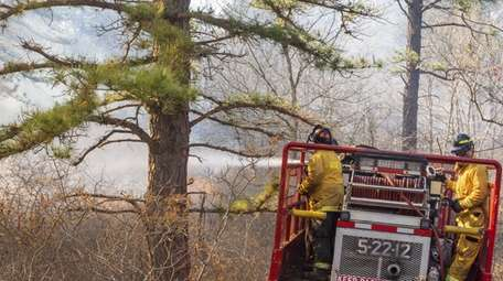 Firefighters battle a brush fire on May 12