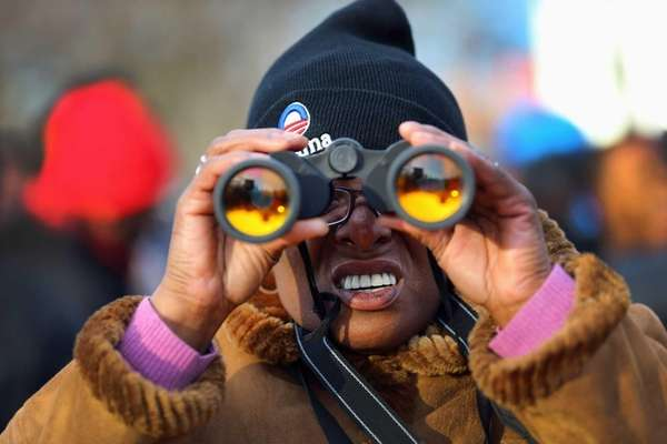 Ednn Daniels uses binoculars as she and others