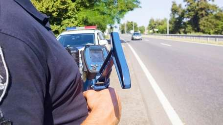 Police officer holding laser speed gun near police
