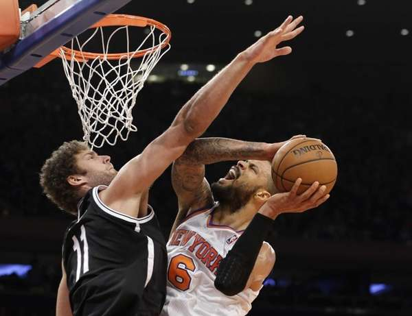 Nets center Brook Lopez (11) fouls Knicks center