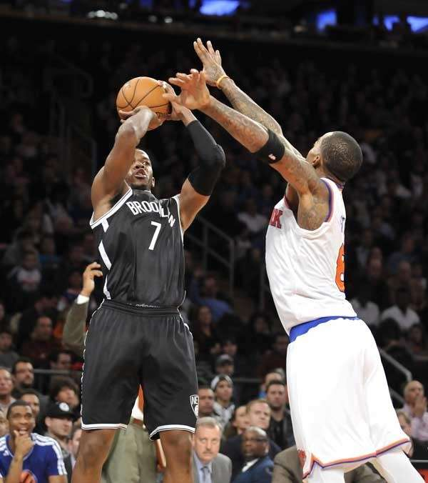 Joe Johnson of the Nets shoots over J.R.