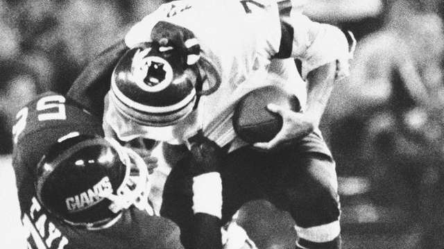 Washington Redskins quarterback Joe Theismann is brought down
