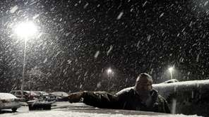 Deepak Tawde, of Plainview, cleans snow off