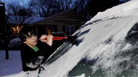 Eric Clemens, 15, scrapes ice from his mother's