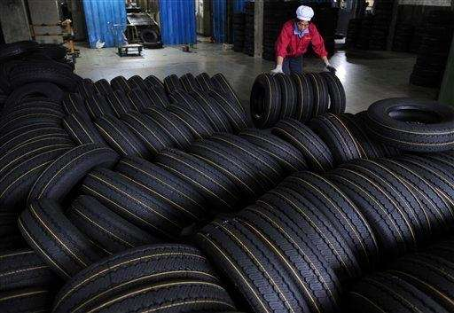A worker moves tires at a tire factory