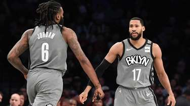 Nets guard Garrett Temple reacts with center DeAndre
