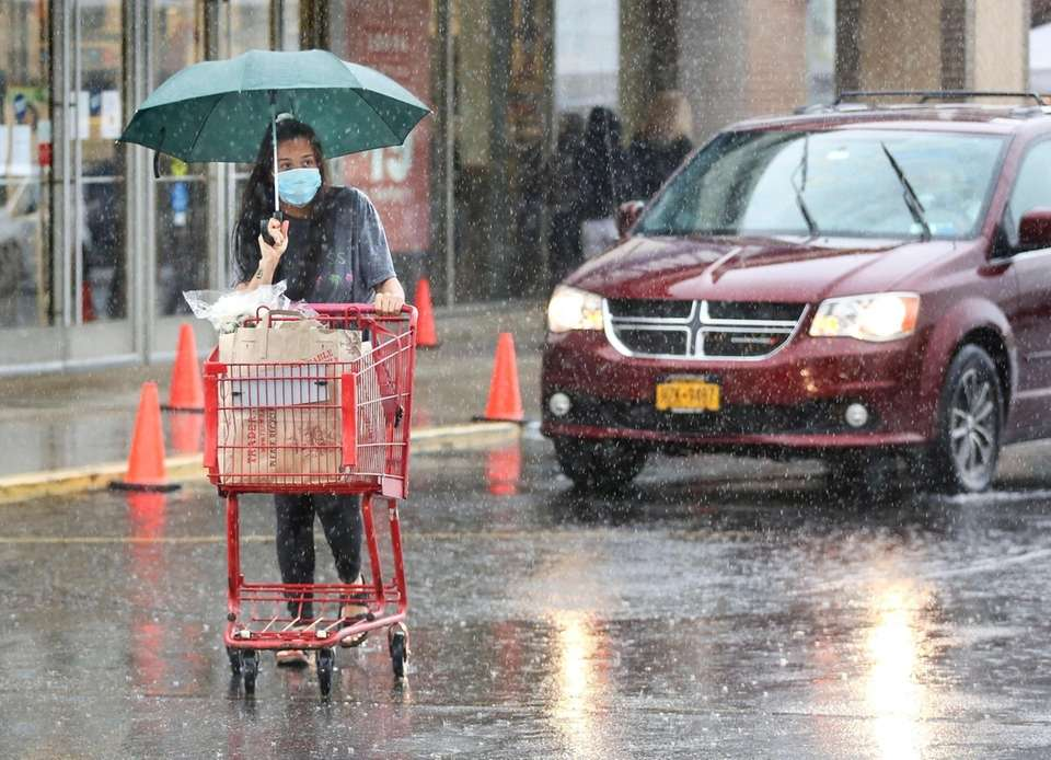 A shopper pushes her cart through the rain