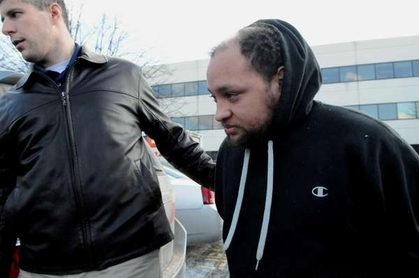 Federal agents escort Angel Rivas, 33, of Shirley,