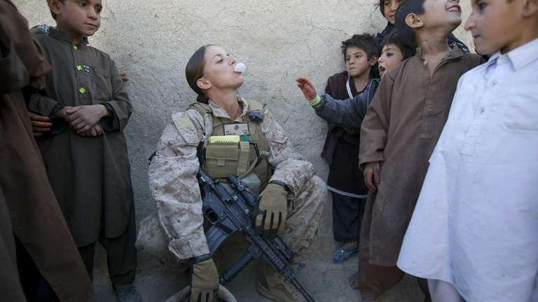 Sargent Sheena Adams, 25, blows bubbles with Afghan