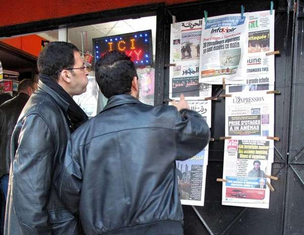 Algerian men look at national newspapers headlining the