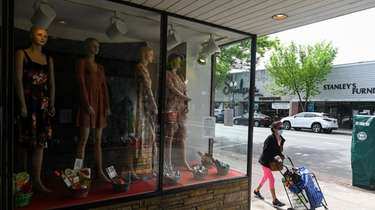A woman walks past Paper Doll Curiosity Shoppe