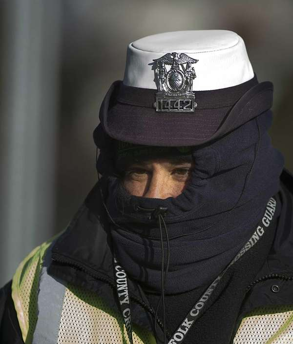 A crossing guard dresses in layers to stay
