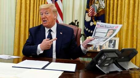 President Donald Trump holds up a copy of
