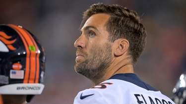 Joe Flacco watches during the second half of