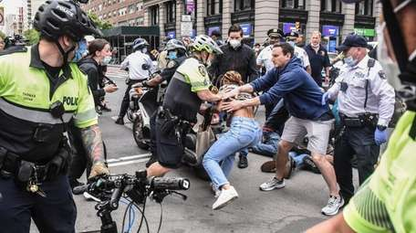 A protester is detained by police during a