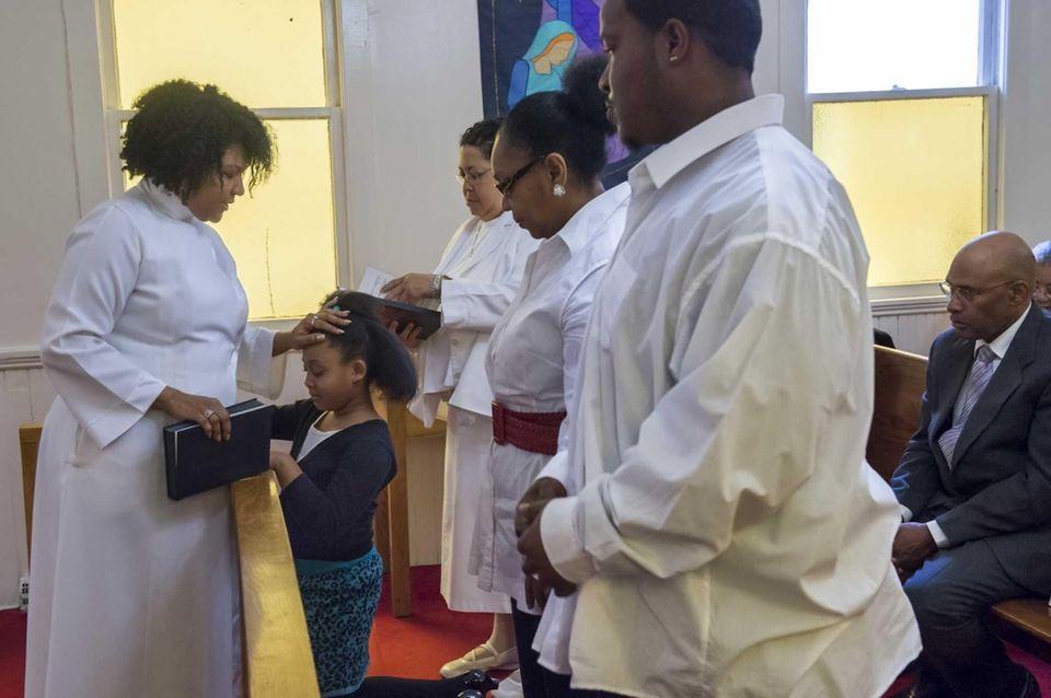 The Rev. Lisa Williamson welcomes Ryann Hudson, 7,