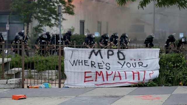 Law enforcement officers protect Minneapolis fire fighters along