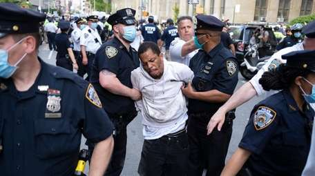 A protester is taken into custody as demonstrators