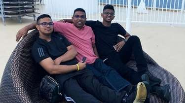 Robin Ramkissoon, center, with his sons, Jonathan, left,