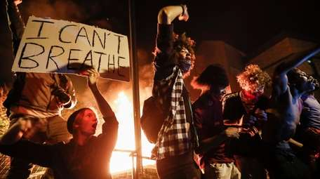 Protestors demonstrate outside of a burning Minneapolis 3rd