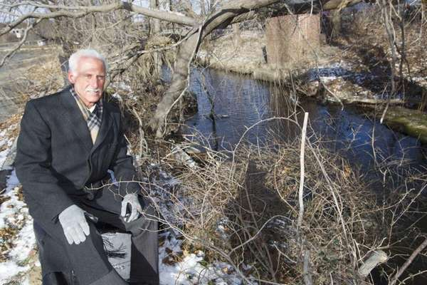 Councilman Timothy P. Mazzei sits by the stream