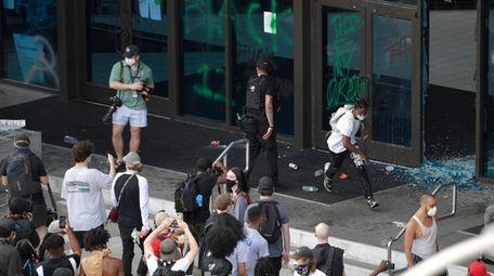 Demonstrators break glass at the entrance to CNN
