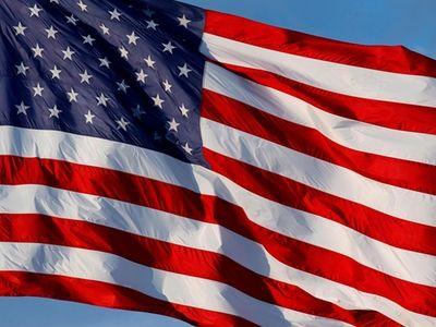 An American flag waves over an auto dealership