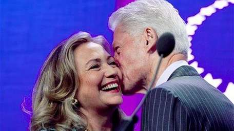 Hillary Rodham Clinton is kissed by her husband,