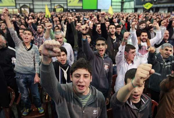 Hezbollah supporters cheer as they listen to a