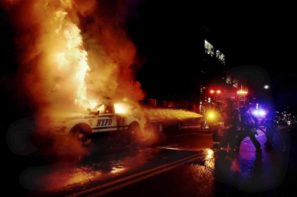 Firefighters work to extinguish a burning NYPD patrol