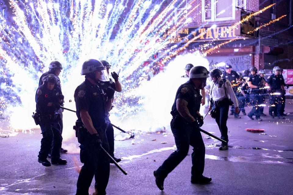 An explosive firework detonates next to police officers