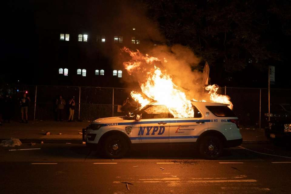 A NYPD vehicle is set ablaze as demonstrators