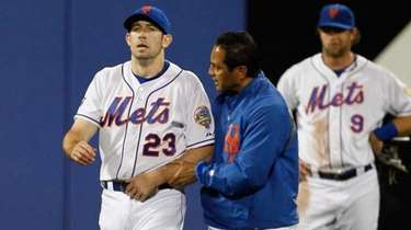 Mets head trainer Ray Ramirez walks Mike Baxter