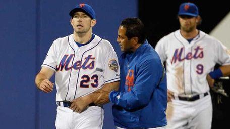 Mets head trainer Ray Ramirez walks Mike Baxter