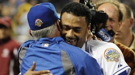 Mets starting pitcher Johan Santana, right, hugs manager