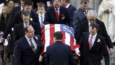 Pallbearers carry the casket containing the body of